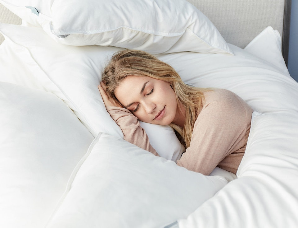 blonde woman sleeping on a kapok and natural latex pillow in a white bed